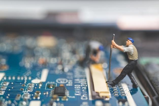 Miniature people: worker team of engineers repairing keyboard computer laptop