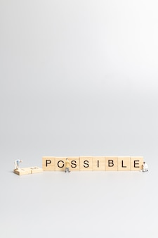 Miniature  people worker team on impossible word in wooden alphabet letters with prefix un crossed out, leaving the word possible