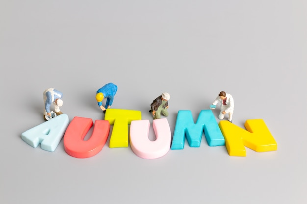 Miniature people worker team painting of autumn with place for text on grey background, hello autumn concept