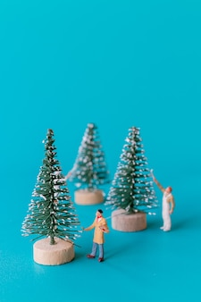 Miniature people , worker team painting on christmas tree , christmas and happy new year concept.