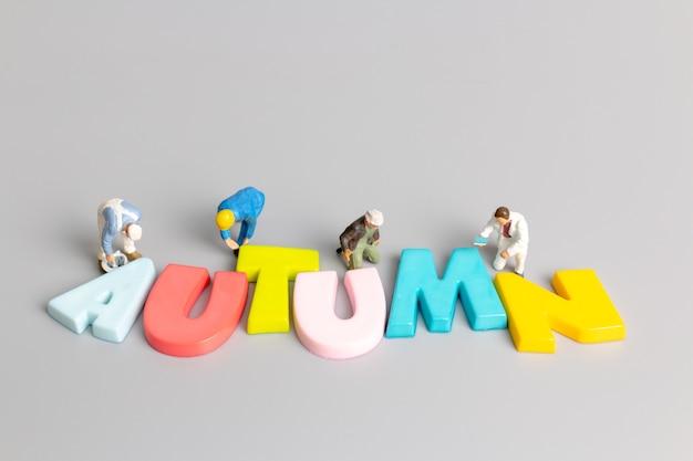 회색 배경에 텍스트를 넣을 수 있는 가을의 미니어처 작업자 팀 페인팅, hello autumn 개념
