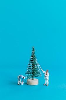 미니어처 사람들, 작업자 팀이 크리스마스 트리, 크리스마스, 새해 복 많이 받으세요 개념에 그림을 그립니다.