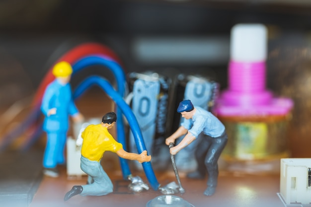 Miniature people: worker team repairing electronic circuits.
