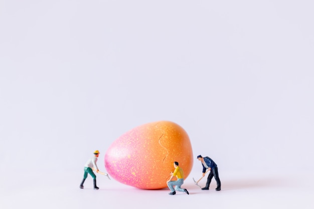 Miniature people worker team working at easter-eggs for easter day background
