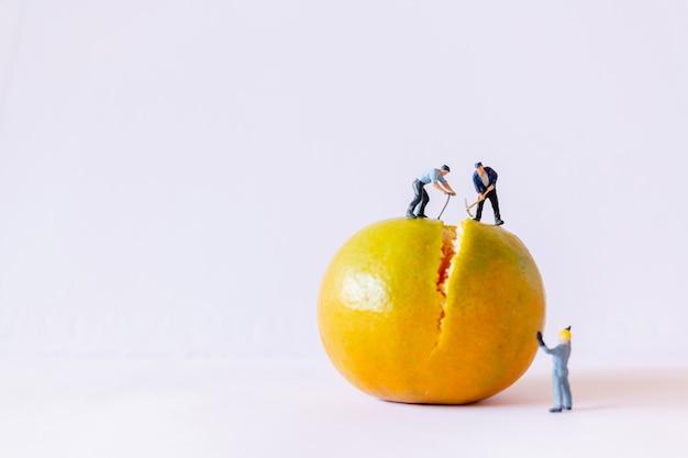 ミニチュアの人々:オレンジ色の背景の上に取り組んでいる労働者チーム