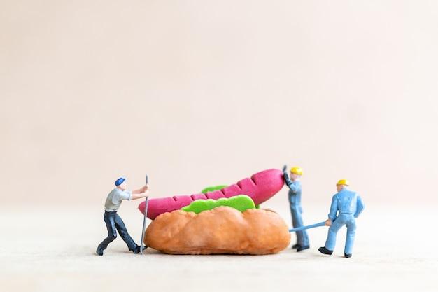미니어처 작업자는 핫도그 빵, 패스트 푸드 및 정크 푸드 개념을 만듭니다.