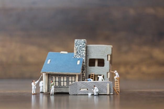 Miniature people: workers team painting a new home.