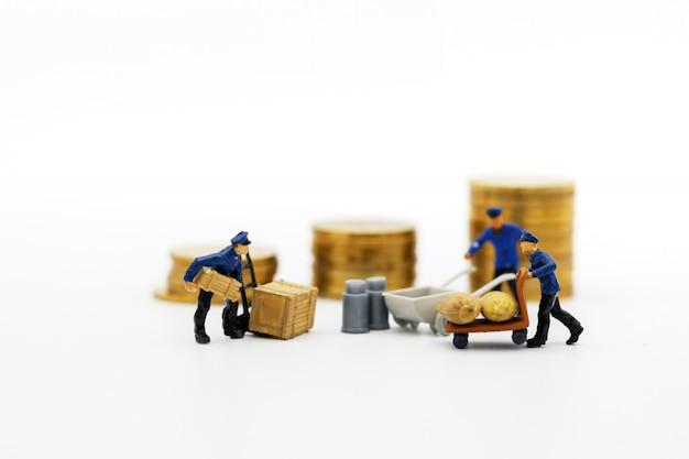 ミニチュアの人々:労働者はコインのお金を輸送します。成功、金融、投資、ビジネスコンセプトの成長。
