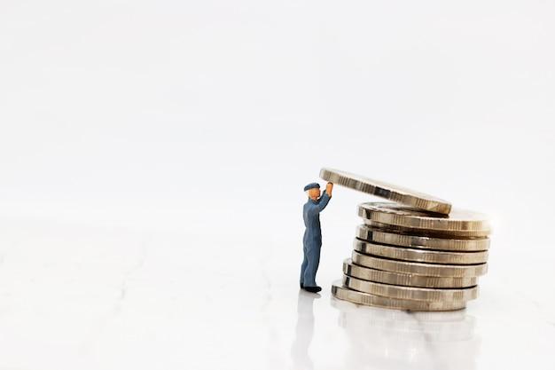 ミニチュアの人々:労働者はコインを運ぶ。