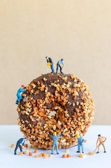 미니어처 사람들이 작업 팀 수제 초콜릿 버터 넛 도넛 만들기