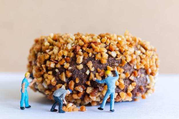 Миниатюрные люди, работающие в команде, делают домашние шоколадные пончики с орехами