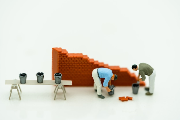 Miniature people working on a wall