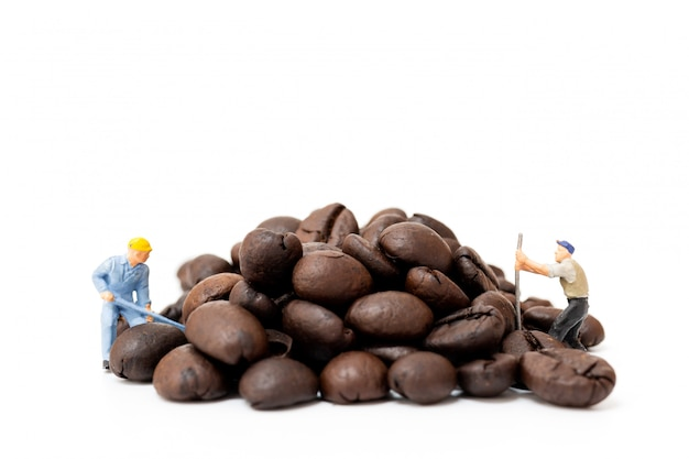 Miniature people working with roasted coffee beans