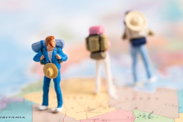 미니어처 사람들 백패커는 세계지도에서 놀라운 발견 여행 여행을 즐깁니다.