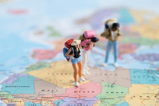 Миниатюрные люди backpacker наслаждаются открытием, путешествием по удивительной карте мира.
