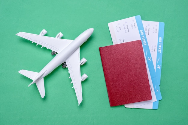 Miniature of the plane, airline tickets and passport on a green background
