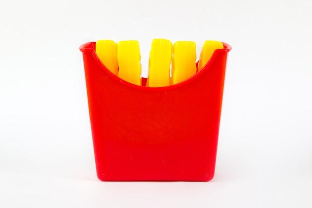 미니어처 감자 튀김 장난감, 흰색 바탕에 장난감 플라스틱 감자 튀김. 유해한 인공 식품의 개념입니다. 패스트 푸드