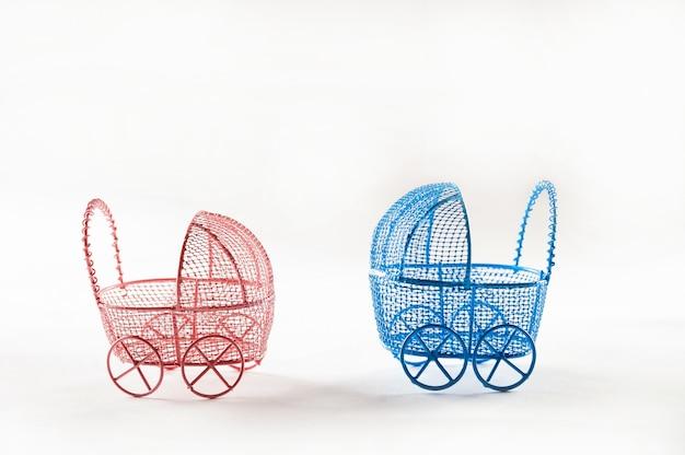 白い背景のクローズアップのミニチュア乳母車。赤ちゃんと妊娠の概念とコピースペース。
