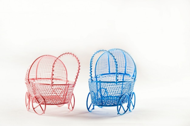 Miniature prams on a white background close-up. baby and pregnancy concept and copy space.