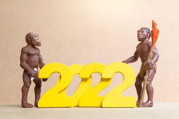 2022年、新年あけましておめでとうございますのコンセプトを祝うミニチュア原始人