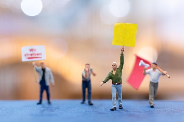 Миниатюрные протестующие держат таблички и протестуют на размытом фоне