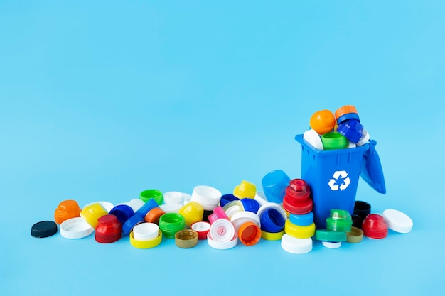 Miniature recycling container filled with plastic bottle caps of different sizes, shapes and colors on light blue.