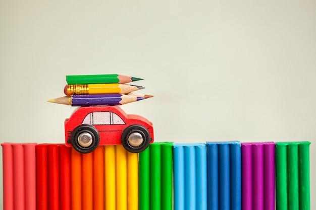 ミニチュア赤い車粘土の多色の壁にカラフルな鉛筆を運ぶ。学校のコンセプトに戻る。