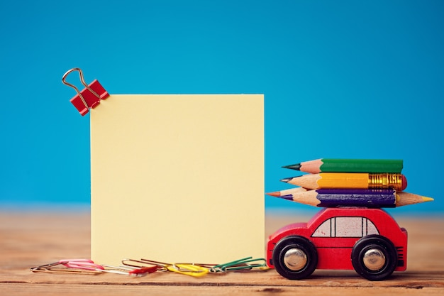 Miniature red car carrying a colorful pencils on blue