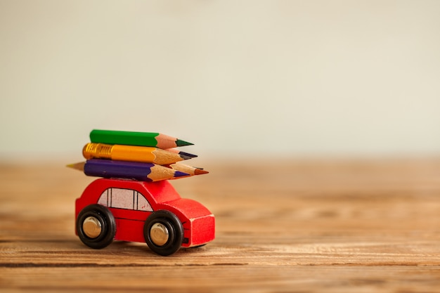 Miniature red car carrying a colorful pencils on wooden table. back to school concept