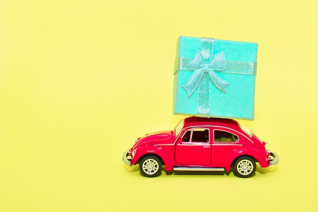 Miniature red car carrying gift box. car delivers gift on yellow background. valentine, postcard