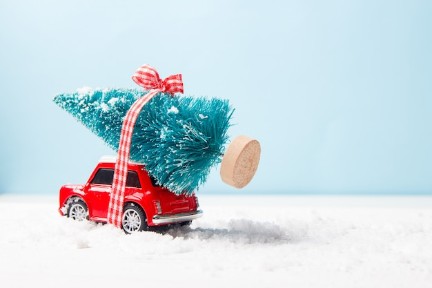 Miniature red car toy delivering christmas tree on blue