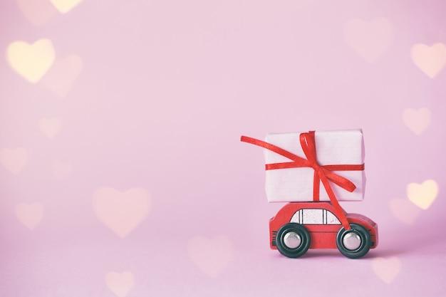 バレンタインデーのためのピンクの壁の屋根にギフトボックスが付いたミニチュアの赤い車。