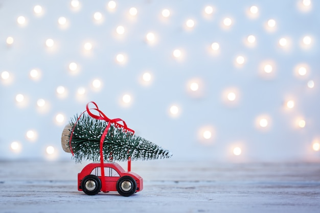 Miniature red car with christmas fir tree on wooden background. holiday concept