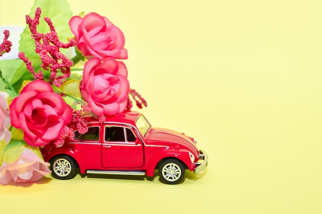 Miniature red retro toy car and a bouquet of flowers, on yellow background. valentine, postcard