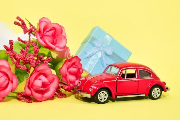 Миниатюрный красный ретро игрушечный автомобиль, цветы и подарочная коробка, на желтом фоне. валентинка, открытка