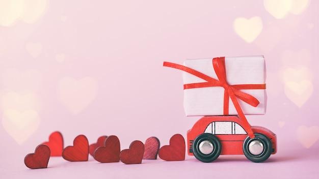 ピンクの壁に赤いハートが付いた屋根にプレゼントボックスが付いたミニチュアレトロな赤い車。