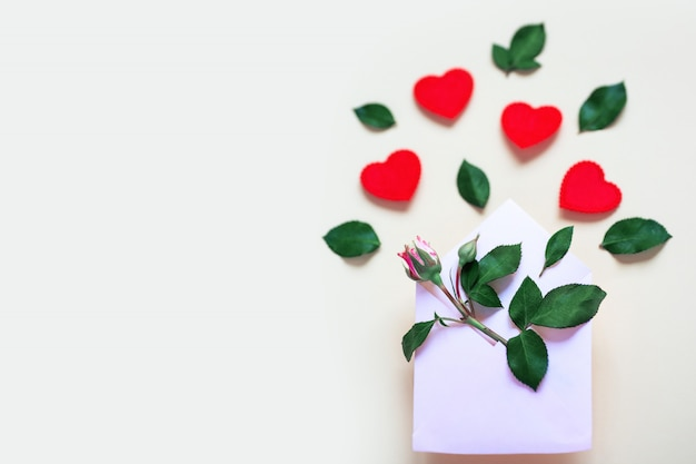 A miniature rose flower with leaves and hearts lies in an envelope.  valentine's day concept.