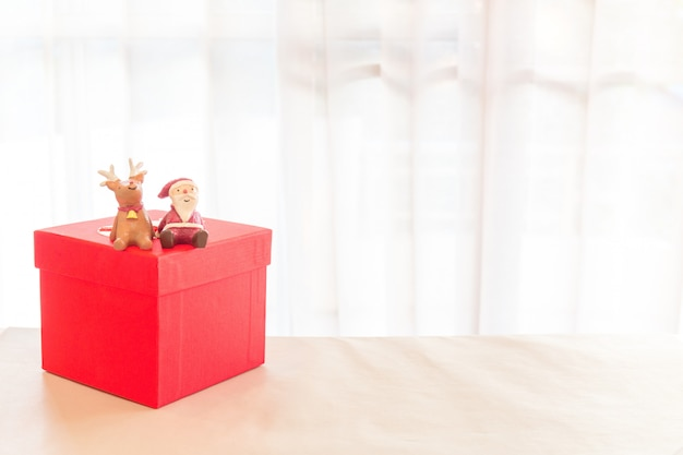 Miniature santa claus and reindeer decoration with packing red parcels box.