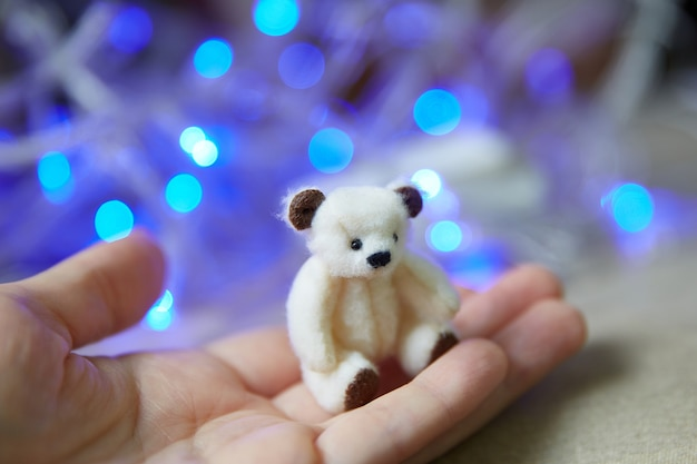 Miniature sewn bear on the palm of your hand. teddy bear polar on the background of blue fairy lights. copyspace.