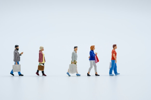 Miniature shopper : men and women hand carry shopping bag and walk on white background