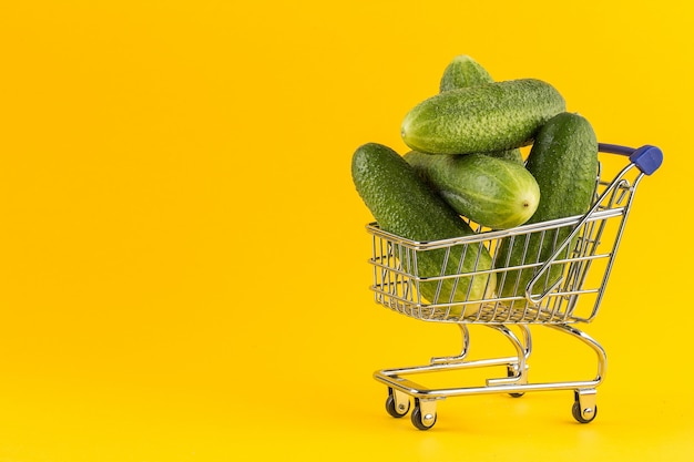 Miniature shopping cart filled with cucumbers on yellow background.