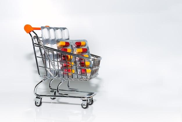 Миниатюрная тележка для покупок, заполненная таблетками и капсулами на белом фоне, концепция медицины и коронавируса.