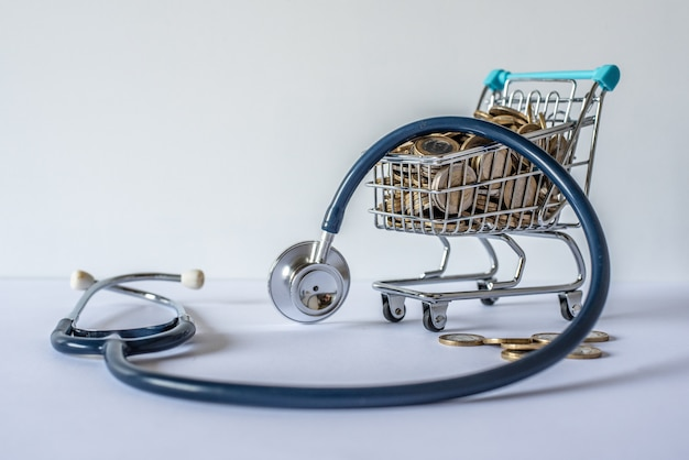 Miniature shopping cart full of coins and a stethoscope