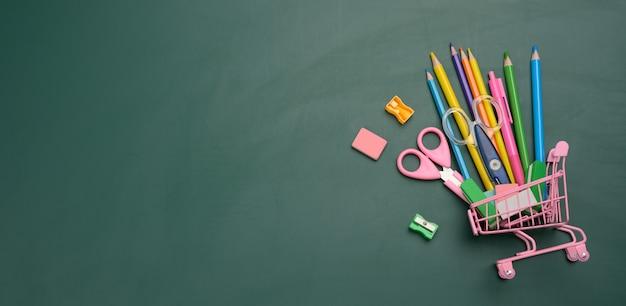 녹색 분필 보드에 학교 사무 용품의 전체 미니어처 쇼핑 카트. 학교 준비, 펜 및 노트북 구입, 평면도, 복사 공간