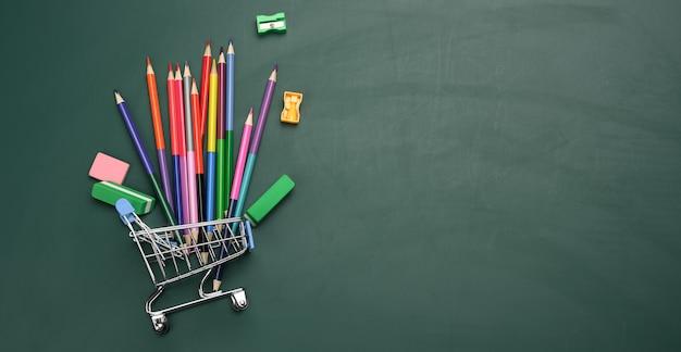 Miniature shopping cart full of school office supplies on a green chalk board. preparing for school