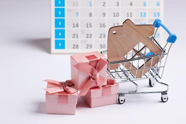 ミニチュアショッピングカート、家の図、白い背景の上のデスクトップカレンダーとギフトボックス。ホリデーショッピング、ブラックフライデー、毎月の特別オファーのコンセプト。住宅購入