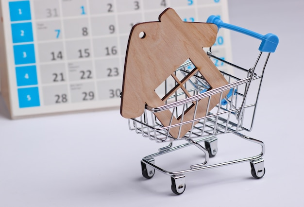 ミニチュアショッピングカート、白い背景の上のデスクトップカレンダーと家の図。ホリデーショッピング、ブラックフライデー、毎月の特別オファーのコンセプト。住宅購入