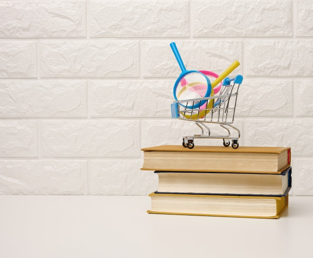 Miniature shopping cart stands on a stack of books, white brick background, order books online, copy space