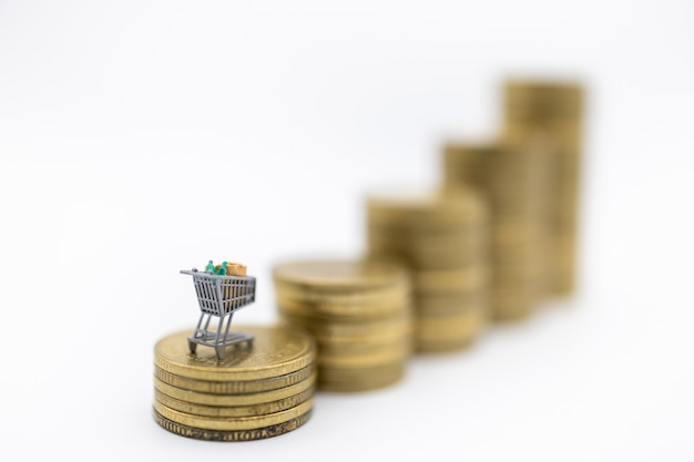 Miniature shopping cart or trolley on top of stack of used gold coins on white