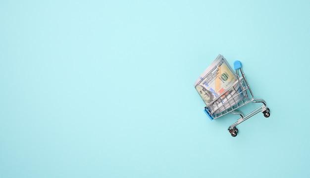 水色の背景に紙の米ドルのスタックとミニチュアショッピングカート。節約、販売、コピースペース
